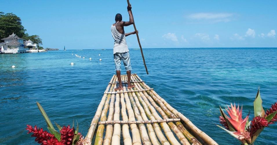 14.mar.2016 - O crescimento jamaicano. Um guia empurra uma canoa de bambu pela praia de Porto Antonio, na Jamaica. O turismo é responsável por boa parte da economia do país: cerca de 10% dos empregos e 27% do PIB
