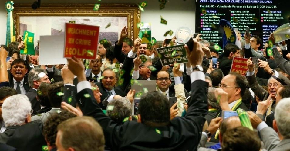 11.abr.2016 - Deputados comemoram jogando bandeiras do Brasil como confetes após maioria dos membros da comissão especial na Câmara votar a favor do parecer do relator Jovair Arantes (PTB-GO), que defende a abertura do processo de afastamento da presidente Dilma Rousseff. A sessão durou quase 10 horas, 38 deputados aprovaram o relatório e 27 se manifestaram contrários