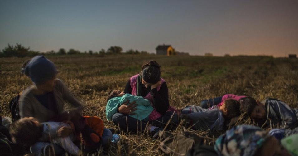 """19.abr.2016 - Rojin Sikho, centro, mulher de Farid Majid, dorme com a filha, Widad, entre outros parentes em um campo de trigo, enquanto eles esperam para atravessar as cercas entre Sérvia e Hungria. Mauricio Lima, Sergey Ponomarev, Tyler Hicks e Daniel Etter do jornal """"The New York Times"""" ganharam o Prêmio Pulitzer com uma série de fotos sobre refugiados na Europa"""
