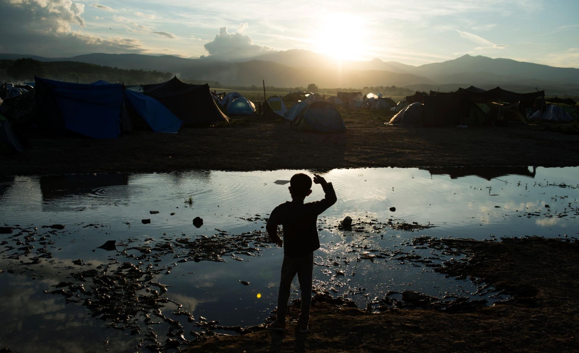 30.abr.2016 - Garoto joga pedras em poça em acampamento de refugiados na fronteira entre a Grécia e a Macedônia. Ao redor de 54 mil pessoas estão retidas na Grécia desde que a rota de migração pelo Bálcãs foi fechada, em fevereiro