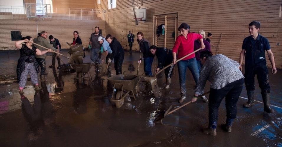 """2.jun.2016 - Voluntários ajudam a remover a lama de um ginásio que ficou inundado durante fortes chuvas em Simbach am Inn, na Alemanha. A polícia afirmou que """"a água subiu tão rápido que praticamente ninguém teve tempo de fugir"""". Quatro mulheres morreram em uma casa inundada na cidade"""