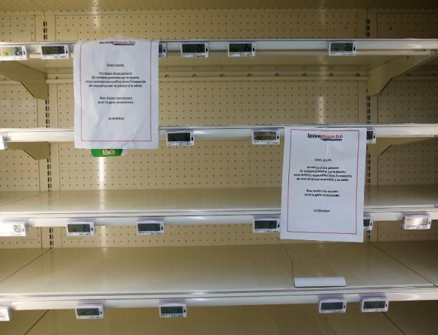 Placas explicando a falta de manteiga são colocadas em prateleiras vazias em um supermercado em Reze, na França