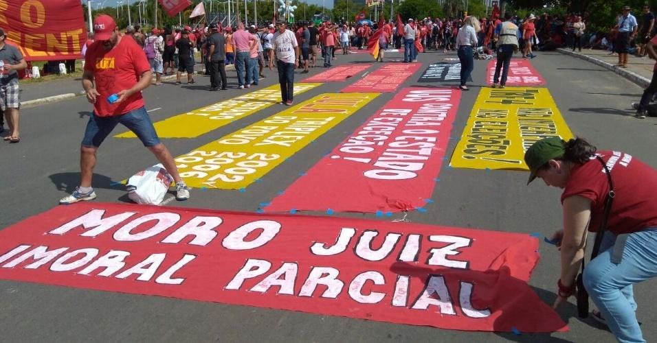 Centrais Sindicais anexam mensagens em defesa da democracia às margens do anfiteatro Pôr do Sol do Guaíba, em Porto Alegre, durante o julgamento do ex-presidente Lula