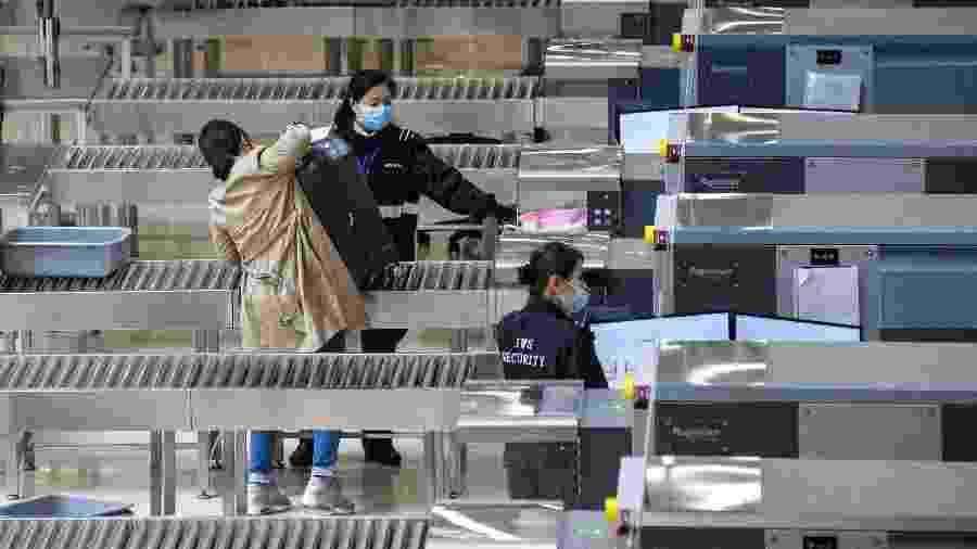 Membros da segurança usam máscaras faciais dentro da estação de trem de alta velocidade que conecta Hong Kong à China continental.  A China pediu aos cidadãos que adiassem as viagens ao exterior para conter o avanço do novo coronavírus - Anthony Wallace/AFP