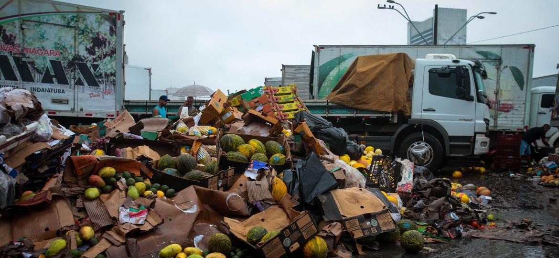 Permissionários da Ceagesp, na zona oeste da capital, descartam alimentos após as fortes chuvas que atingiram a cidade na segunda-feira - Felipe Rau/Estadão Conteúdo