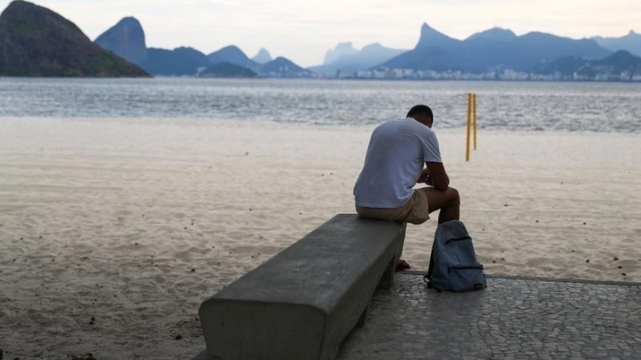 Homem na deserta praia de Icaraí, em Niterói, durante pandemia de coronavírus; parcela da população brasileira no desemprego ou informalidade é preocupação agravada com crise na saúde - Pilar Olivares/Reuters