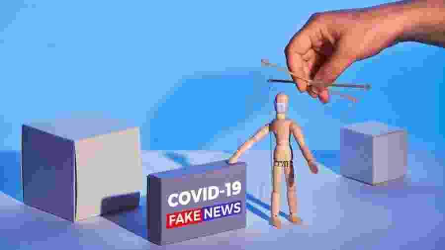 """Ilustração gráfica mostra boneco de madeira controlado por mão, como um fantoche, ao lado de caixa que diz: """"Covid-19 Fake news"""" - Getty Images"""