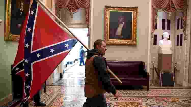 06 jan. 2021 - Manifestante favorável ao presidente Donald Trump carrega bandeira dos estados confederados ao invadir Congresso dos Estados Unidos - MIKE THEILER/REUTERS - MIKE THEILER/REUTERS