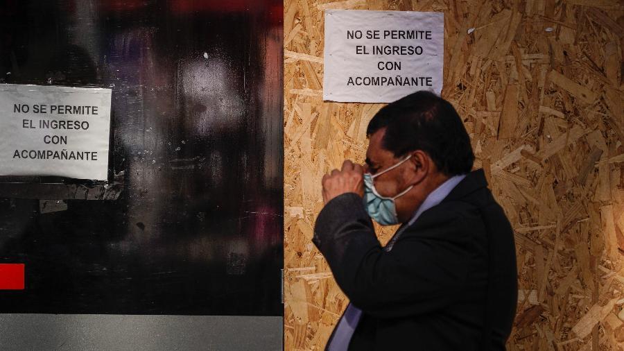 21.jun.2021 - Homem caminha e ajusta sua máscara em meio à pandemia de coronavírus em Bogotá, Colômbia. No mesmo dia, o país superou 100 mil mortes por covid-19 - Diego Cuevas / Getty Images