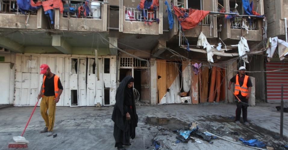 23.jul.2015 - Trabalhadores iraquianos limpam calçada um dia depois de um ataque com carro-bomba em uma zona comercial de Bagdá. Atentados a bomba mataram ao menos 21 pessoas e feriram dezenas, nesta quarta-feira, em bairros de maioria xiita da capital iraquiana