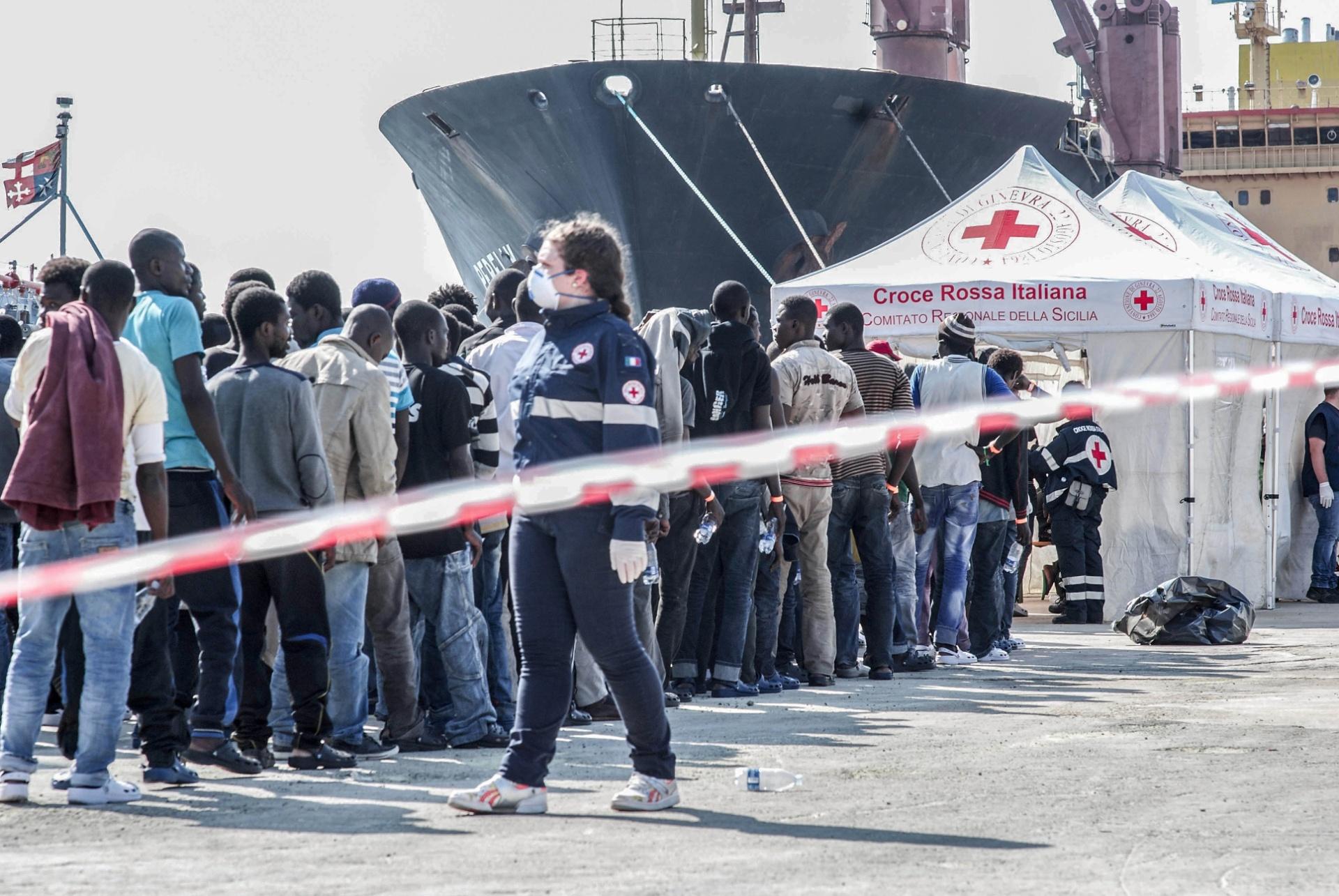 2.out.2015 - Assim que os refugiados chegam em navios no porto de Augusta, na Sicília, Itália, são organizados em filas para receber atendimento imediato da Cruz Vermelha, que pergunta sobre sintomas, dores, febre e até gravidez