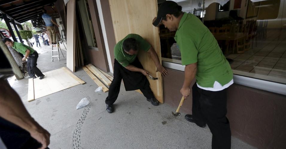 23.out.2015 - Funcionários de restaurante cobrem janelas com placas de madeira, enquanto o furacão Patricia se aproxima, no balneário de Puerto Vallarta, no Mèxico