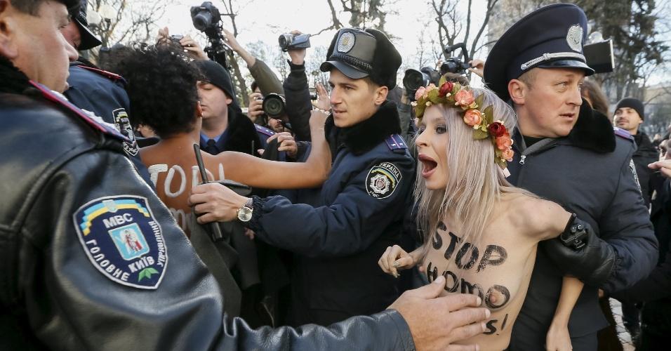 12.nov.2015 - Policiais detêm uma ativista do grupo Femen durante protesto contra homofobia do lado de fora do prédio Parlamento, em Kiev, na Ucrânia. O Femen e grupos ligados ao direito dos homossexuais estão pressionando o Parlamento para que aprovem lei que proíbe discriminação no local de trabalho com base na sexualidade, entre outras medidas