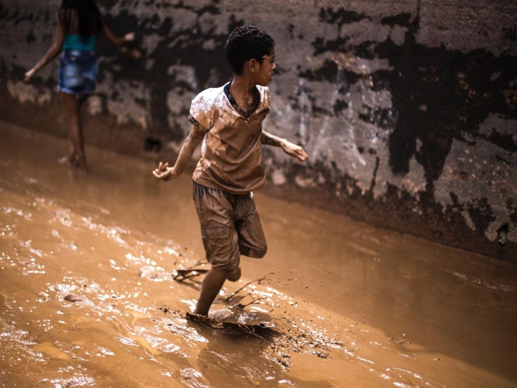 12.MAR.2016 - Criança brinca em rua coberta de lama após a água baixar, em Franco da Rocha (SP), neste sábado (12). O temporal dos últimos dias causou enchentes e deixou mortos e desaparecidos na região metropolitana