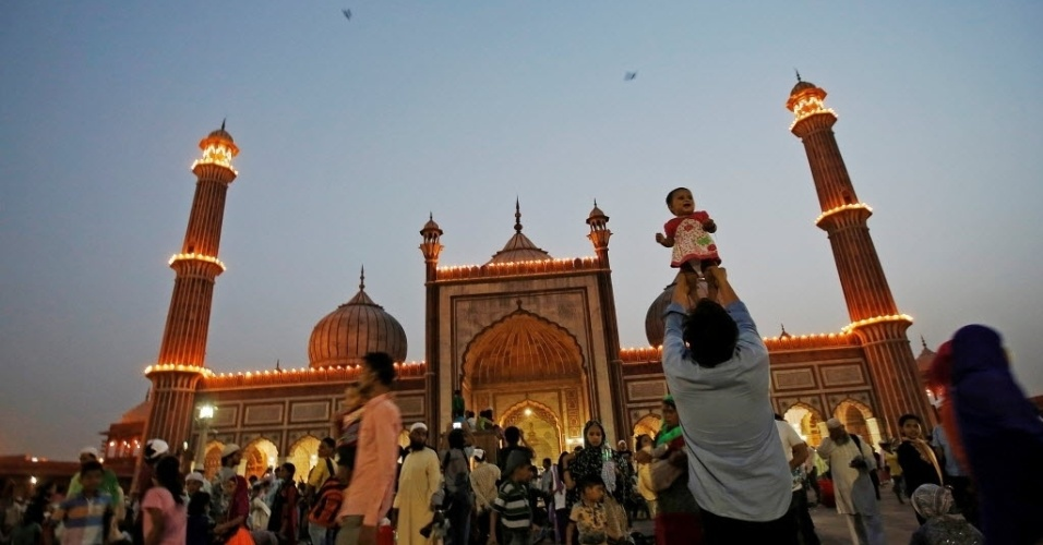 14.jun.2016 - Pai ergue o filho após a quebra do jejum diário, durante o mês sagrado do Ramadã, em frente à Grande Mesquita, na parte antiga de Nova Déli, na Índia