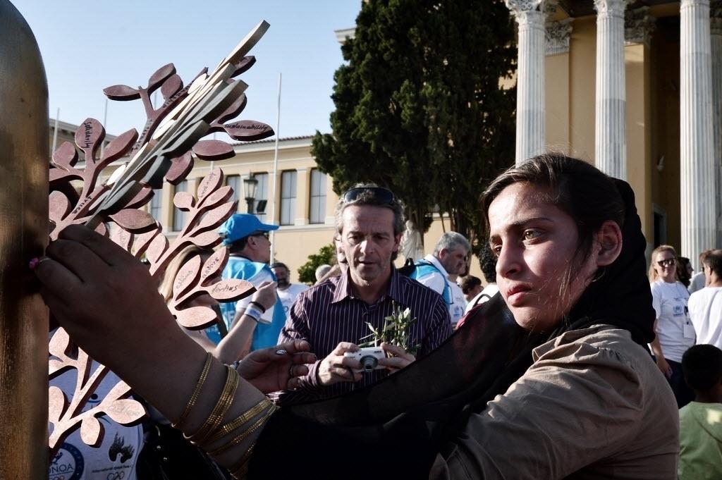 22.jun.2016 - Uma menina que está morando em um campo para refugiados nos arredores de Atenas, na Grécia, coloca um ramo de oliveira com mensagens de esperança durante evento celebrando a semana do Dia Mundial dos Refugiados.