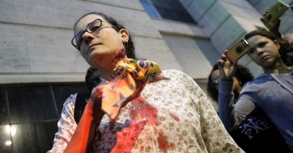 28.abr.2017 - Uma manifestante ficou ferida após a polícia militar entrar em confronto com um grupo de black blocs no centro do Rio de Janeiro, nesta sexta-feira. A PM atirou balas de borracha e bombas de gás lacrimogêneo contra os manifestantes, que revidaram com pedradas e bombas caseiras