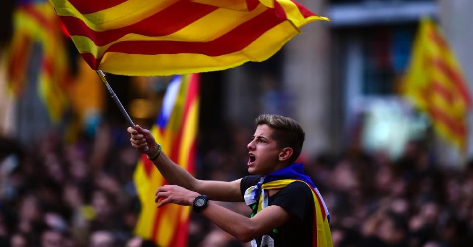 27.out.2017 - Menino segura a bandeira da Catalunha em meio a multidão que celebra a declaração de independência da Espanha, em Barcelona