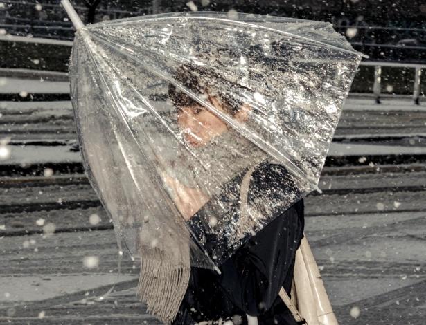 7.mar.2018 - Mulher se protege de nevasca em Manhattan, Nova York, EUA