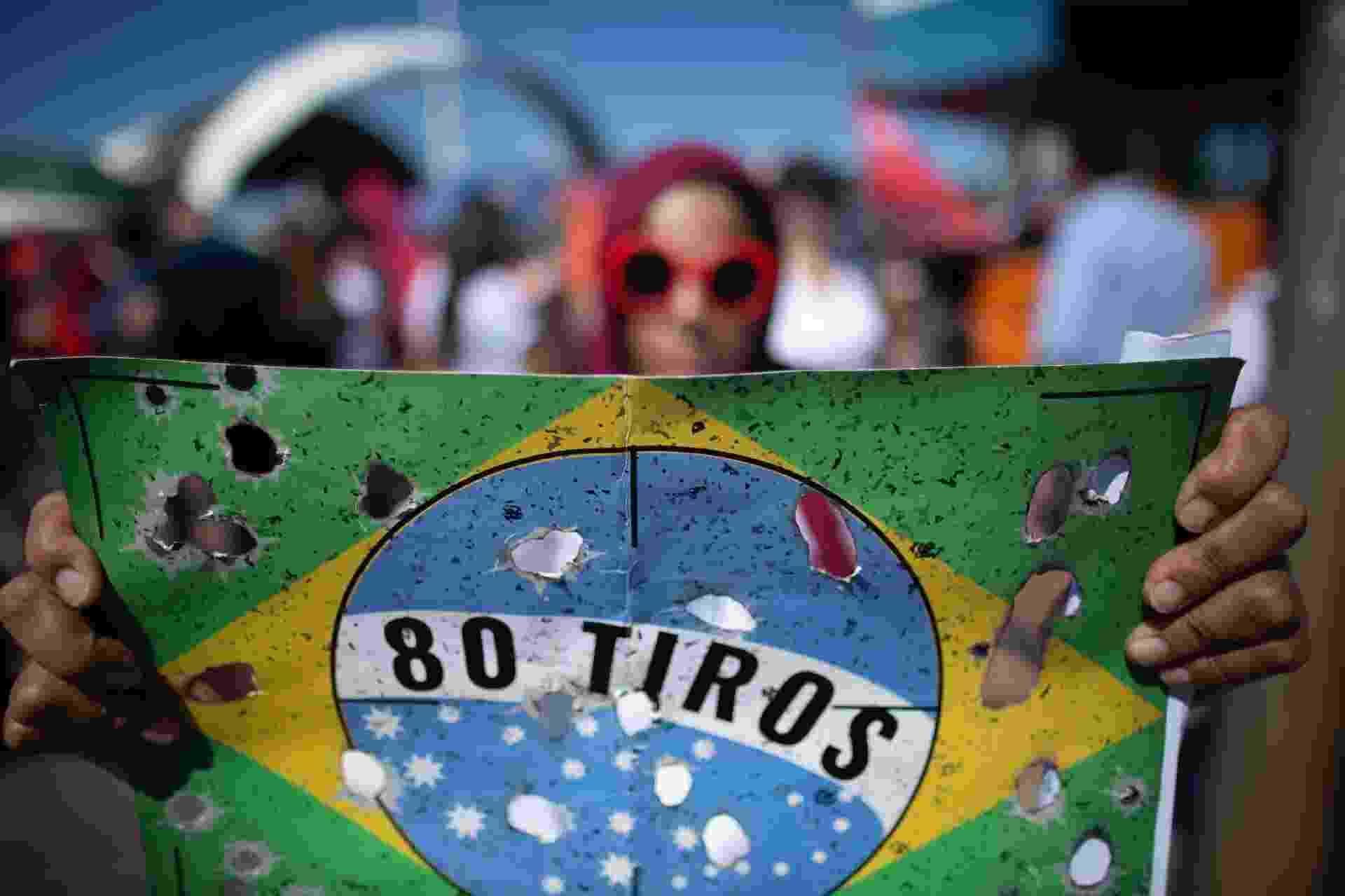 30.mai.2019 - Em Brasília, manifestante lembrou o caso dos 80 tiros, disparados por homens do Exército e que levaram à morte o músico Evaldo dos Santos Rosa e o catador de recicláveis Luciano Macedo, em 7 de abril, em Guadalupe, na zona norte do Rio - Myke Sena /Fotoarena/Folhapres