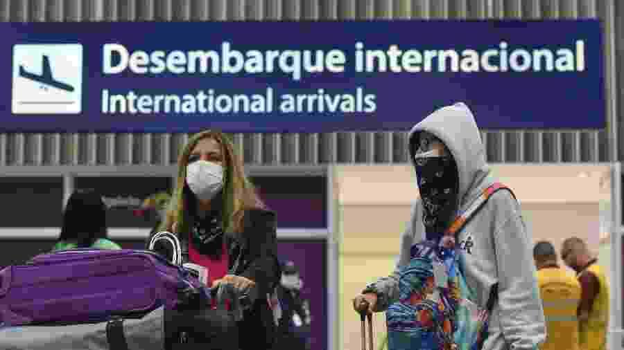 Passageiros desembarcam com máscaras no Aeroporto do Galeão, no Rio de Janeiro, em meio à pandemia de coronavírus - Fabio Teixeira/NurPhoto via Getty Images