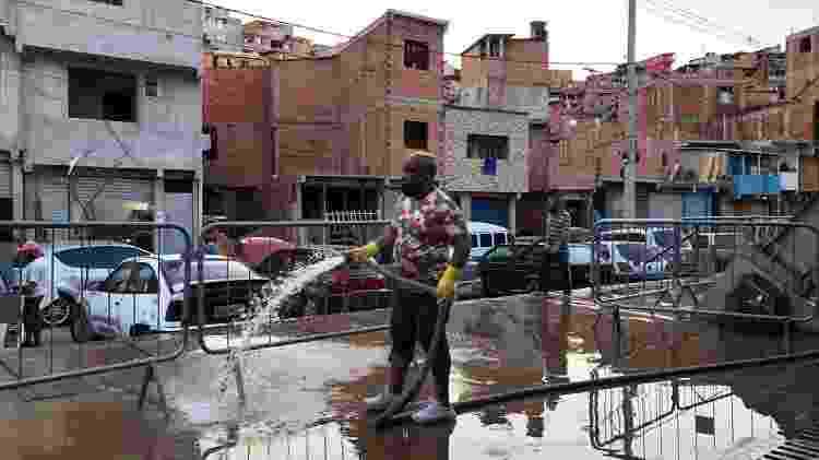 Morador de Paraisópolis lava calçada da entrada do gabinete de crise da covid-19 na favela - Gabriela Sá Pessoa/UOL - Gabriela Sá Pessoa/UOL