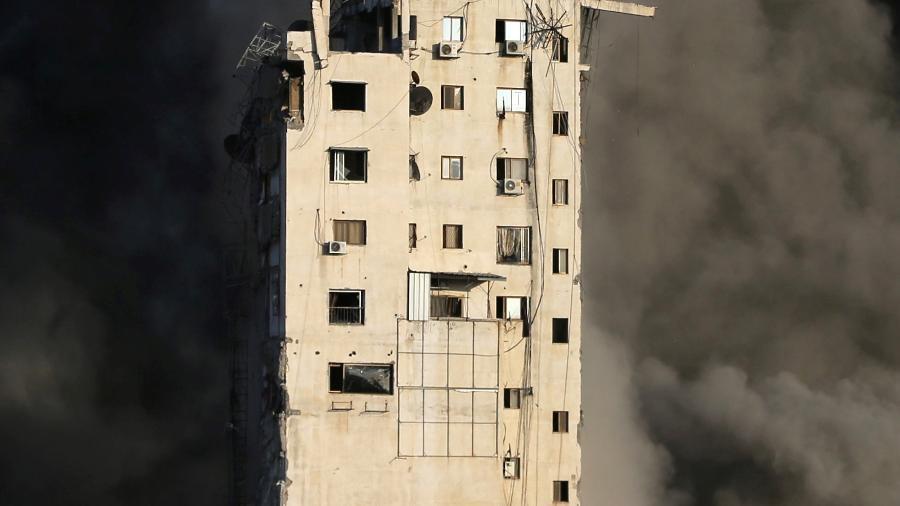 Fumaça sobe de um prédio destruído por ataques aéreos de Israel durante o conflito na Palestina - Ibraheem Abu Mustafa/Reuters