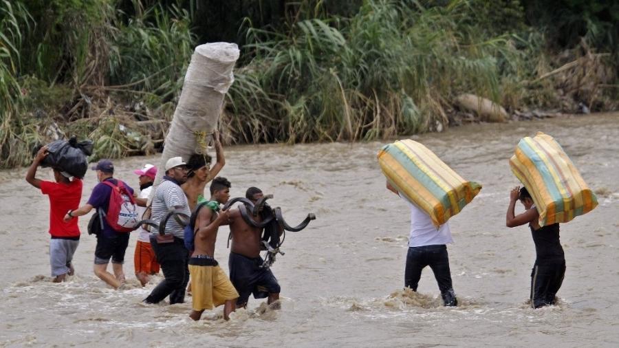 Foto mostra imigrantes venezuelanos cruzando a fronteira entre Venezuela e Colômbia na região da cidade colombiana de Cucuta - 19.nov.2020 - Schneyder Mendoza/AFP
