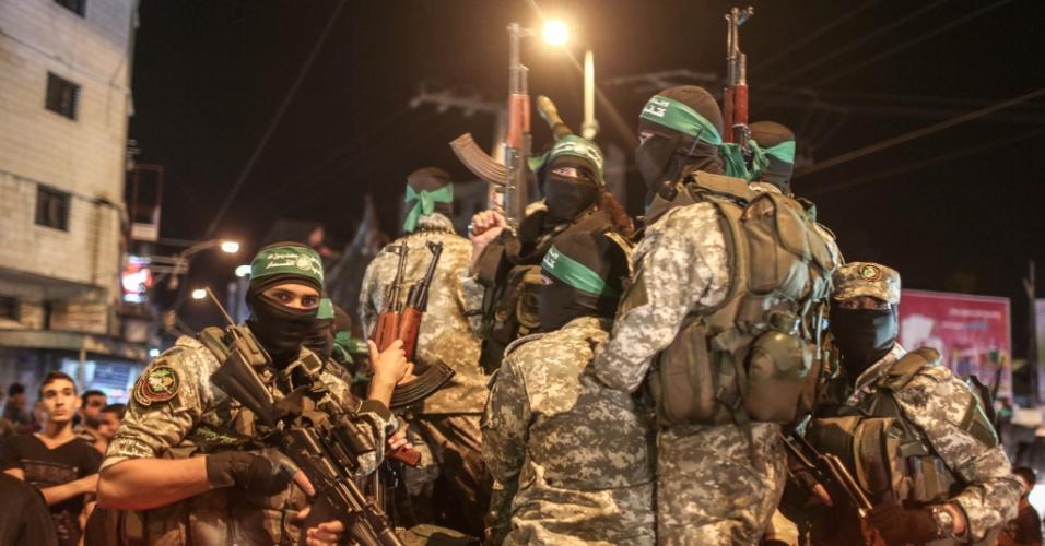 8.jul.2015 - Palestinos da brigada de Ezzedine al-Qassam, braço armado do Hamas, seguram suas armas durante uma marcha militar na cidade de Gaza, nesta quarta-feira (8), para marcar o primeiro aniversário da guerra em grande escala travada por Israel na faixa de Gaza