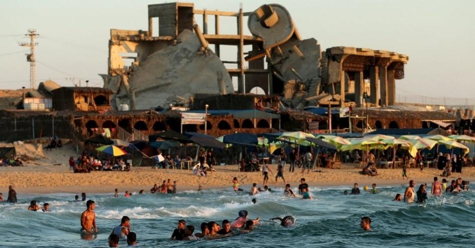 14.ago.2015 - Palestinos tomam banho no mar Mediterrâneo, perto de edifício que foi destruído por bombardeio israelense, no norte da faixa de Gaza