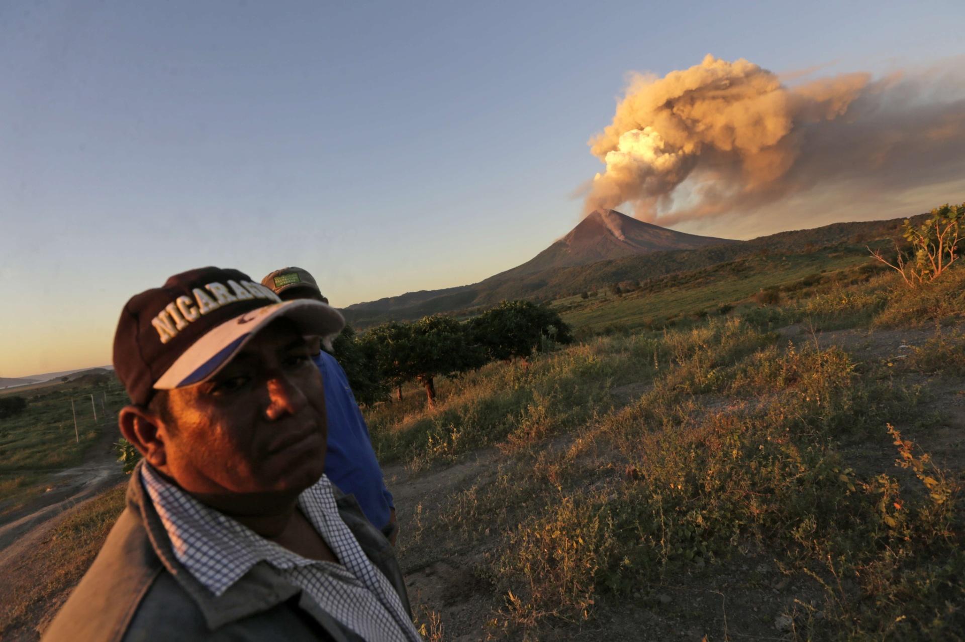 2.dez.2015 - Homem observam o vulcão Momotombo expelindo fumaça e cinzas da comunidade de Papalonal, em León, na Nicarágua. O vulcão, que é o maior do oeste do país, soltou uma coluna de gás e cinzas de um quilômetro de altura na terça-feira (1º), acendendo na população o temor de que o gigante acorde após 110 anos de inatividade