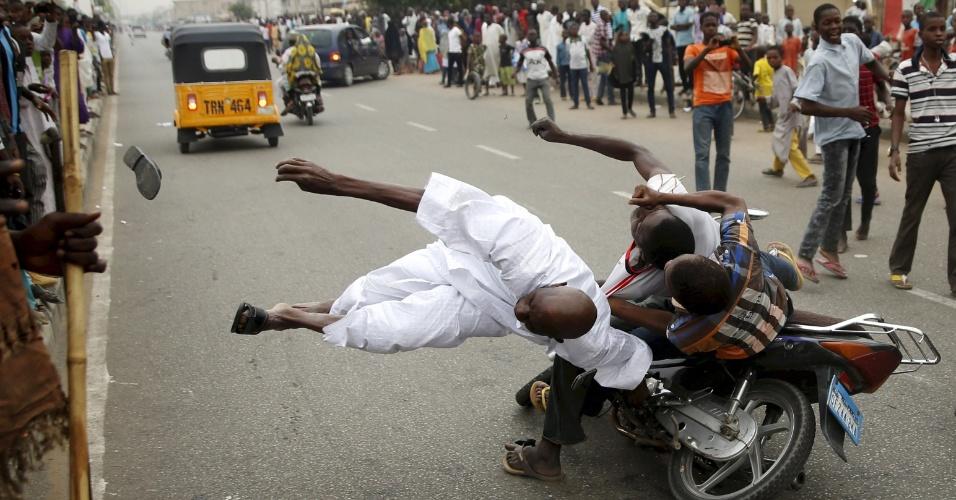 31.mar.2015 - Apoiadores do candidato presidencial Muhammadu Buhari e seu partido All Progressive Congress atinge outro correligionário com uma moto durante as celebrações em Kano, na Nigéria