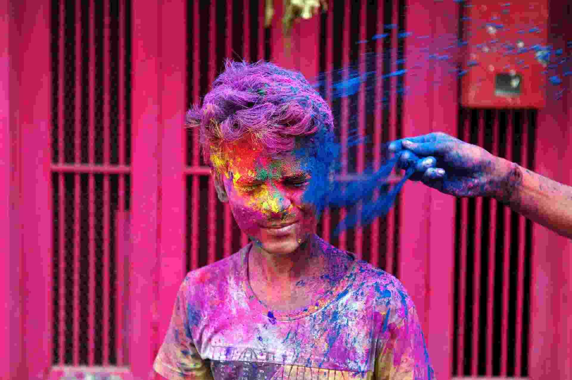 """24.mar.2016 - Indiano recebe pó colorido no rosto durante celebração do festival Holi em Chennai, no sul da Índia. O festival hindu do Holi, também conhecido como """"festival das cores"""", anuncia a chegada da primavera e do fim do inverno no hemisfério norte - Arun Sankar/AFP"""