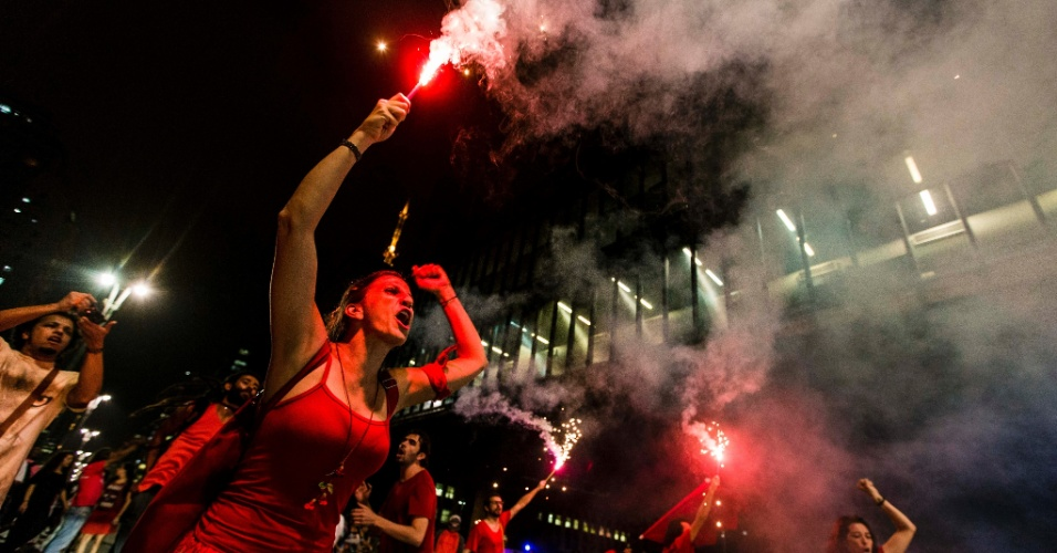 """30.mar.2016 - Jovens gritam palavras de ordem enquanto erguem sinalizadores durante ato denominado """"Arte pela Democracia"""", no vão livre do Masp, na avenida Paulista, em São Paulo. Com música, dança e poesia, diversos artistas estiveram no local para protestar a favor da democracia e contra o impeachment da presidente Dilma Rousseff"""