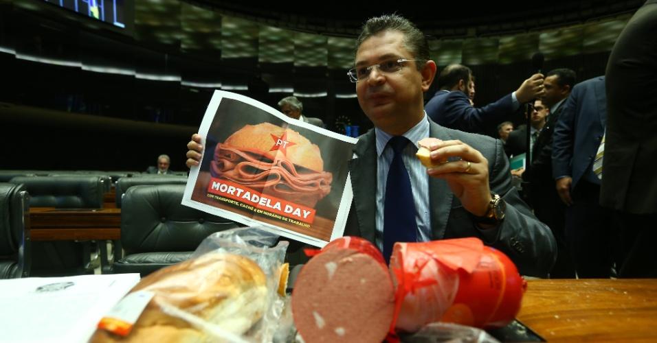 31.mar.2016 - O deputado Sóstenes Cavalcante (PSD-RJ) come e distribui sanduíches de pão com mortadela durante sessão plenária da Câmara dos Deputados, em Brasília. O pão com mortadela se tornou referência aos militantes e apoiadores do Partido dos Trabalhadores