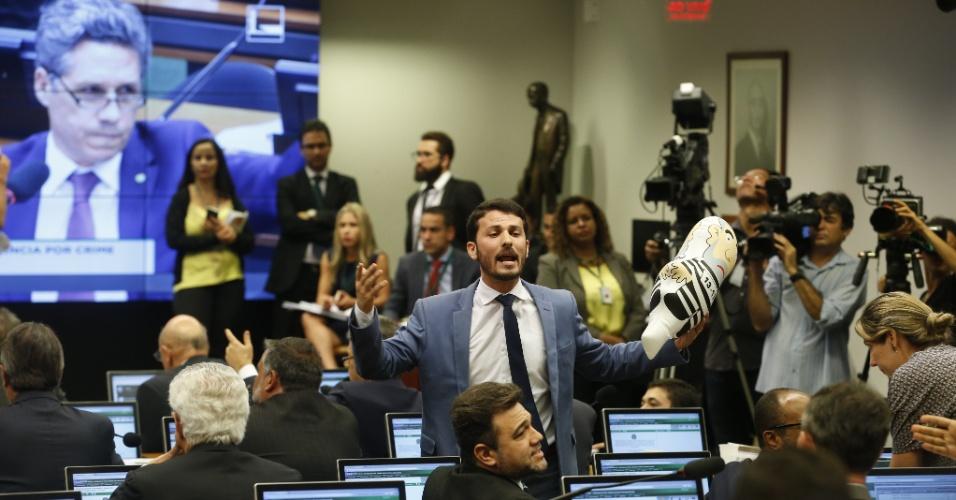 """4.abr.2016 - O deputado federal Marcelo Aro (PHS-MG) segura um """"puxuleco"""" durante audiência da comissão especial do impeachment, na Câmara dos Deputados"""