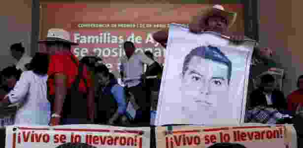 """Bernardo Franco, pai de um dos estudantes desaparecidos de Ayotzinapa, segura cartaz com foto do filho e os dizeres """"foi levado vivo"""", na Cidade do México - Ginnette Riquelme/Reuters"""