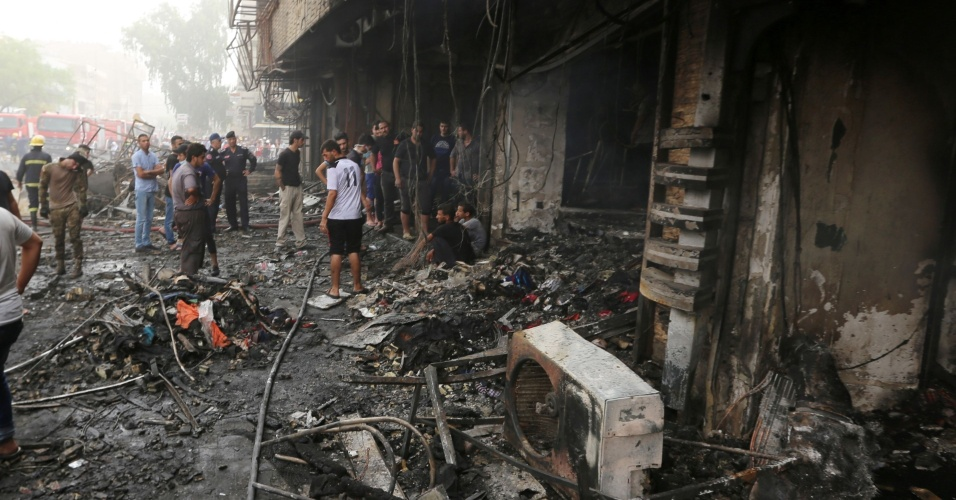 3.jul.2016 - Iraquianos inspecionam local no centro de Bagdá onde ocorreu a explosão de um carro bomba em atentado reivindicado pelo grupo terrorista Estado Islâmico. Pelo menos 75 pessoas morreram e mais 160 ficaram feridas no duplo ataque ocorrido na manhã deste domingo. A  segunda explosão aconteceu pouco tempo depois da primeira, numa zona mais ao leste da capital