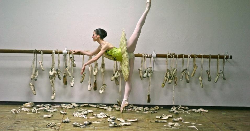 Bailarina posa rodeada por todas as sapatilhas que usou na vida. Por causa do esforço e exigência do balé, as sapatilhas podem durar apenas por uma performance