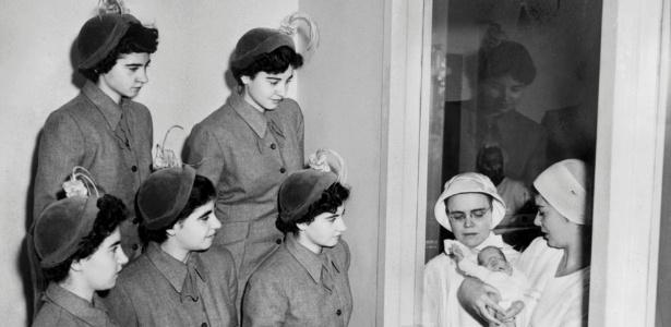 As quíntuplas Dianne, Yvonne, Cecile e Marie, na primeira fila, e Emilie e Annette acima, observam bebê prematuro em hospital nos EUA em 1950