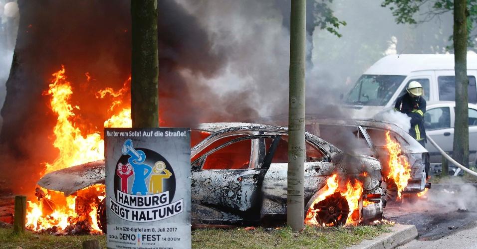 7.jul.2017 - Bombeiro trabalha para apagar fogo ateado em carro em Hamburgo, no primeiro dia da cúpula do G20, na Alemanha