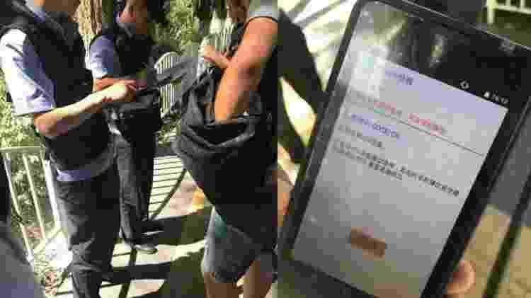 Policiais conferem se smartphones de cidadãos em Xinjiang estão com o app JinWang instalado - Divulgação/Hong Kong Free Press