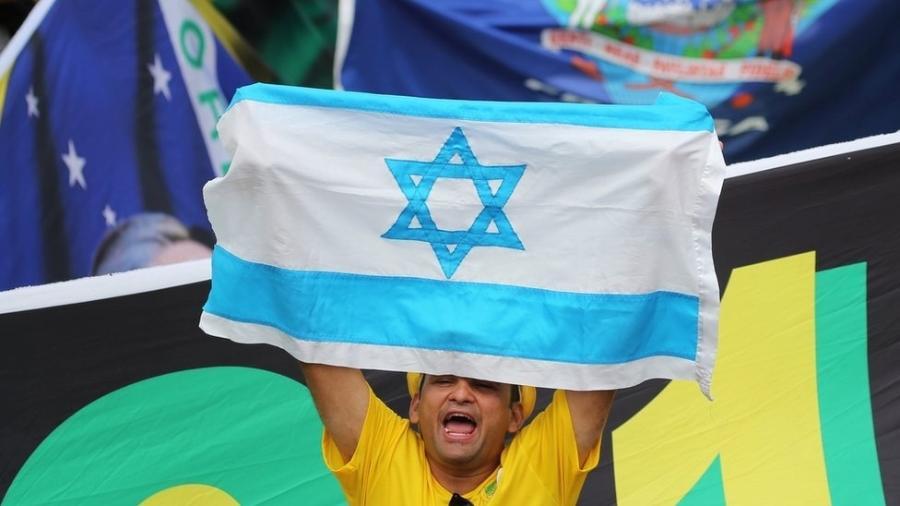Homem levanta bandeira de Israel durante posse de Bolsonaro em Brasília; presidente prometeu, durante campanha, transferência de embaixada para Jerusalém - Reuters