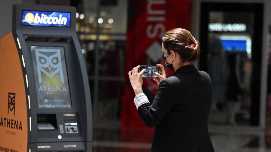 24.jun.2021 - Mulher tira foto de caixa eletrônico de Bitcoin, após sua inauguração pela Athena Bitcoin Inc. em um shopping center de San Salvador, em El Salvador - MARVIN RECINOS / AFP