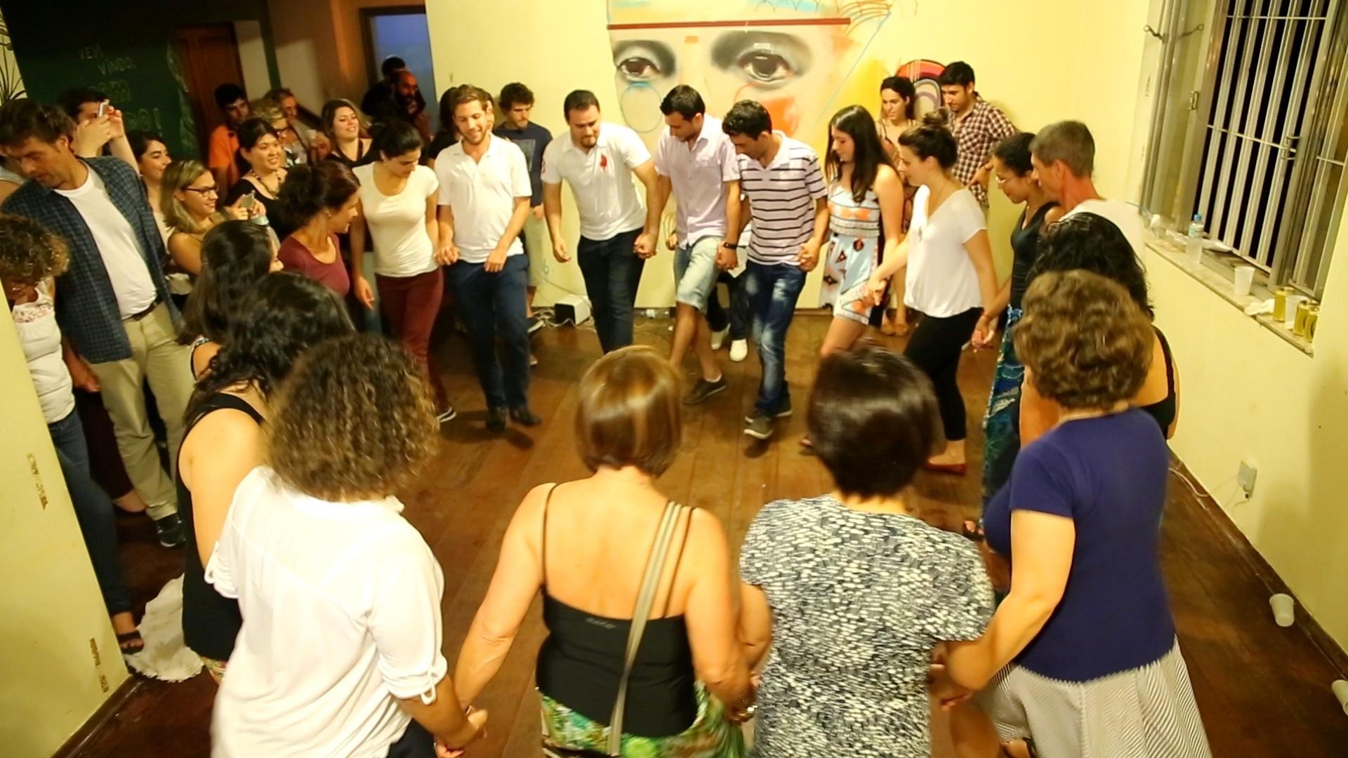 Ali Jeratli, refugiado sírio e professor de árabe da ONG Abraço Cultural, mostra alguns passos da dança tradicional síria para alunos da organização em aula cultural em São Paulo
