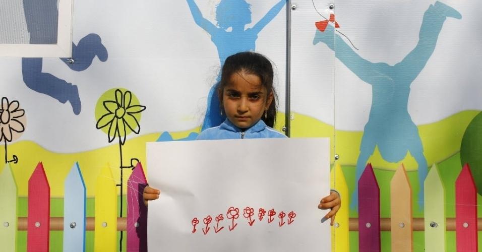A menina síria Reyyan Emin, 7, mostra seu desenho de dentro do campo de refugiados de Yayladagi, na província de Hatay, na Turquia, perto da fronteira com a Síria. A guerra civil na Síria, que já deixou centenas de milhares de mortos, empurra outros tantos para o exílio, entre muitos deles crianças. Os desenhos das crianças do acampamento mostram memórias de suas casas, traumas vividos e esperanças para o seu futuro. Dos 2,3 milhões de refugiados sírios que vivem na Turquia, mais da metade são crianças