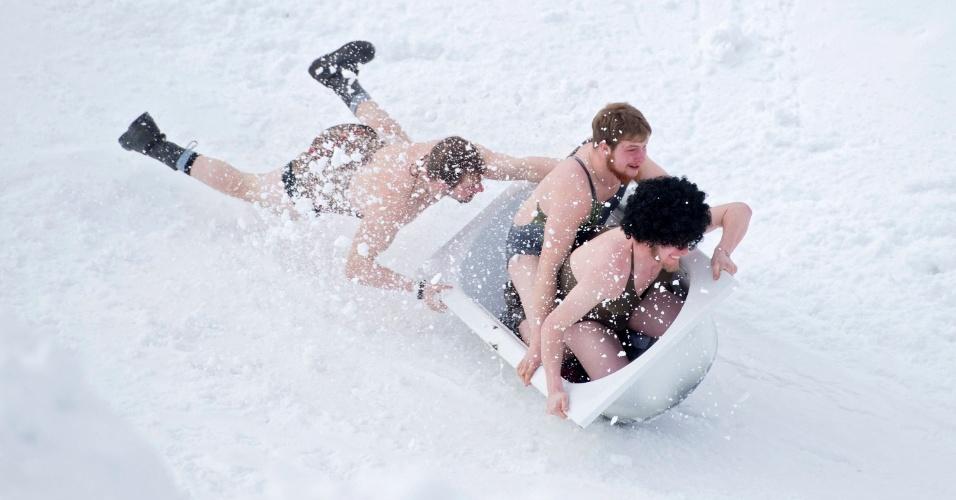 23.jan.2016 - Em meio à neve e o frio, competidores seminus deslizam por ladeira em uma banheira na cidade de Stoos, Suíça. O local recebe a 4º Corrida em Banheiras
