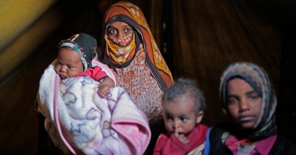 26.mar.2016 - Mãe posa para foto com os filhos em um acampamento de pessoas deslocadas pela guerra na periferia de Amran, no Iêmen. A imagem foi feita pela fotógrafa Rawan Shaif, que visitou hospitais de Médicos Sem Fronteiras em Amran e Haydan durante viagem por cidades das áreas controladas pelos houthis no norte do Iêmen, entre outubro de 2015 e fevereiro deste ano. Há exatamente um ano tinha início os bombardeios da coalizão árabe contra os houthis. Segundo a ONU (Organização das Nações Unidas), 3.218 civis morreram e 5.778 ficaram feridos nos bombardeios