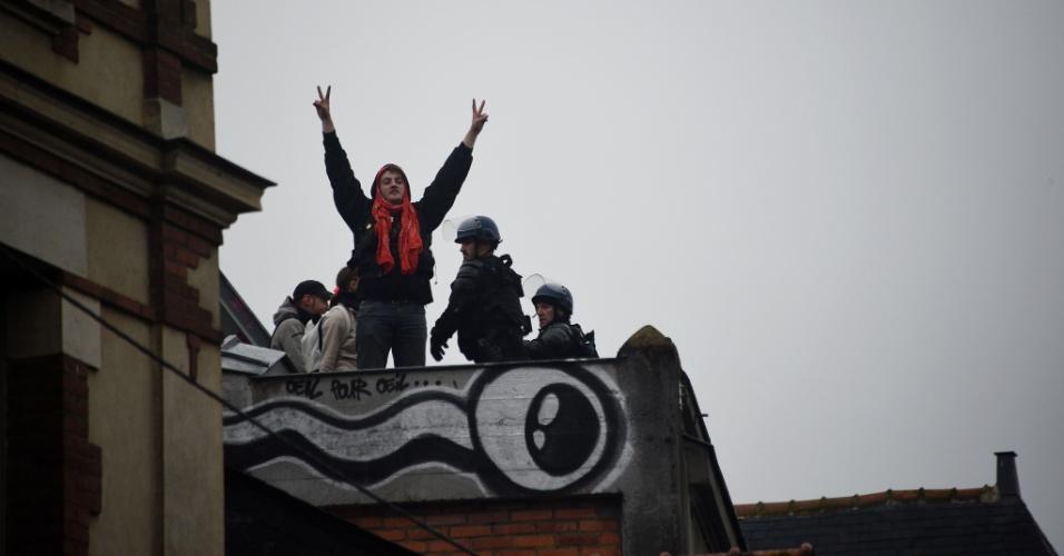 13.mai.2016 - Ativistas gesticulam no telhado da Casa do Povo, em Rennes, no oeste da França, enquanto policiais evacuam o prédio, ocupado desde 1º de maio por manifestantes contrários à proposta de reforma trabalhista do governo François Hollande. O governo francês superou nesta quinta um voto de não confiança proposto após o executivo forçar a análise da proposta