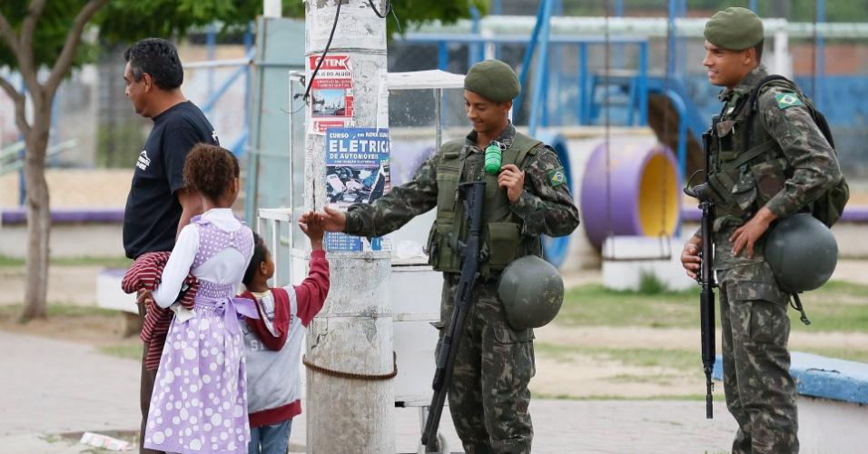 1º.out.2016 - Antes da votação deste domingo (2), militares reforçam a segurança no Rio de Janeiro em áreas controladas por milícias. Soldados ainda se entrosaram com crianças no bairro de Cabuçu, em Nova Iguaçu